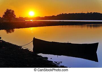 Old boat in sunset on danube river