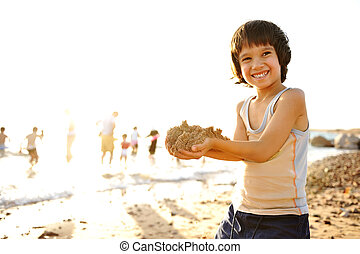 Kid on beach in sand playing, people around, summer hot nice...