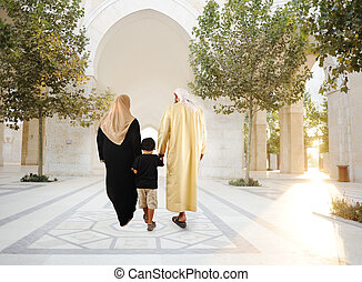 Muslim arabic traditional oriental family walking together, beautiful ambient in front of the mosque