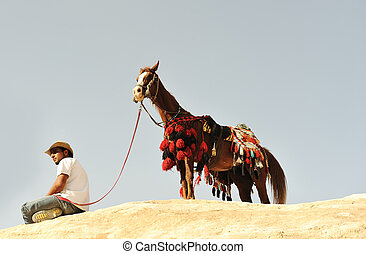 Man with a horse in asian mountains