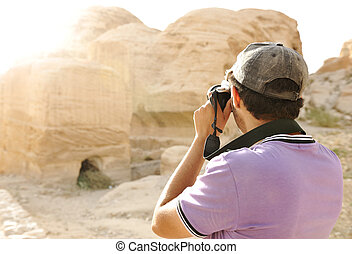A tourist taking a photo of old archeological ruins