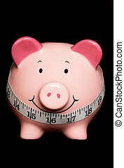 Piggy bank with tape measure isolated on black