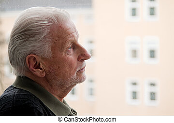 Senior stands sadly in window - a senior is lonely,...
