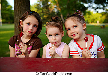 Sisters eating candy - Three sisters sitting at a picnic...