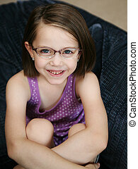 Cute little girl wearing glasses - Little girl sitting on a...