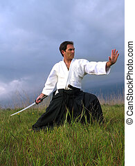 Katana - Man practicing Aikido with a sword and with typical...