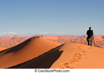 A photographer taking a picture in the desert
