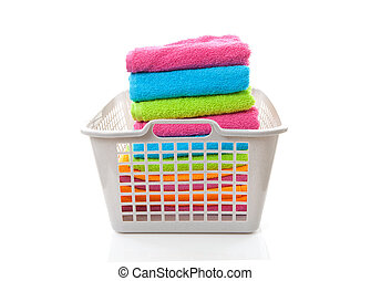 Laundry basket filled with colorful folded towels over white...