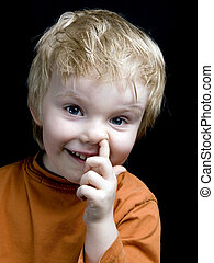 Nose picker - Little boy picking nose and smiling, on black...