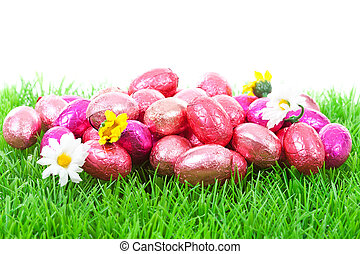 Pink easter eggs on grass over white background