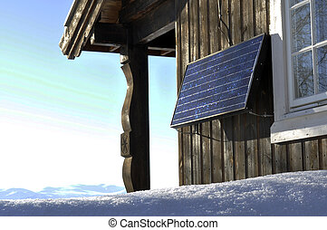solarpower - a solarpanel at a cottage wall