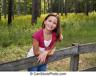 Young Girl on Fence - Young girl in pink leaning on a board...
