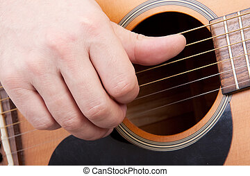 playing the guitar - hand is playing the guitar in closeup