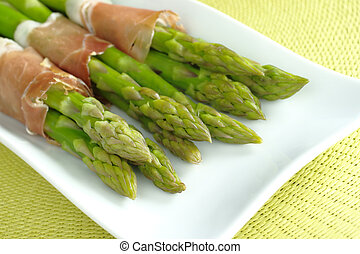 Green asparagus with ham (Selective Focus, Focus on the asparagus heads in the front)