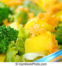 Mango on fresh salad broccoli, mango, carrot, lettuce in a...