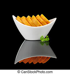 Cooked sweet potato slices (lat. Ipomoea batatas) in white bowl garnished with a parsley leaf and photographed on black  (Selective Focus, Focus on the front)