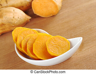 Cooked sweet potato (lat. Ipomoea batatas) cut in slices in white bowl on wooden surface with sweet potatoes in the background (Selective Focus, Focus on the sweet potato in the bowl)