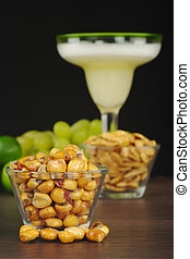Canchas: Peruvian roasted corn eaten as snack with the cocktail called Pisco Sour in the back with limes and grapes (Selective Focus, Focus on the front)