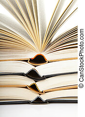 pile of open books in closeup over white background