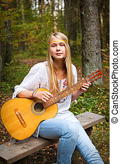 Guitar Player Girl - Beautiful blond guitar player girl in...