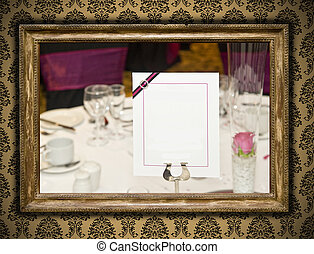 Wedding image in antique gilded frame on vintage damask style wallpaper