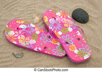 pink slippers - pink colored summer slippers lying on sand