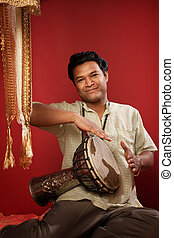 Indian Man Playing Tabla - Smiling young Indian man playing...