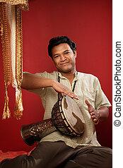 Indian Man Playing Tabla - Smiling young Indian man playing...