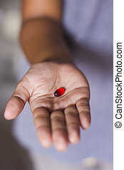 pill on hand - a red tablet is handed out by a woman.