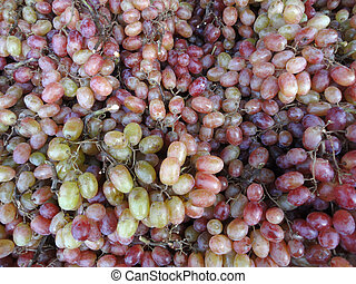 Pile Grapes that colors are amix of green and purple on...