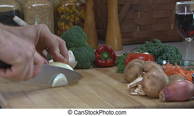 Slicing Onions - Caucasian man slices onions on a cutting...