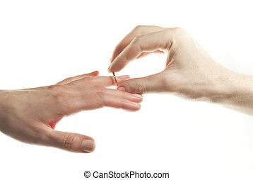 Man's hand passing through the ring onto woman's finger