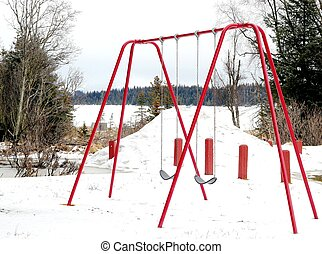 Red swing-set in winter - A bright red swing-set in an empty...