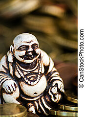 Laughing Budda in front of coins