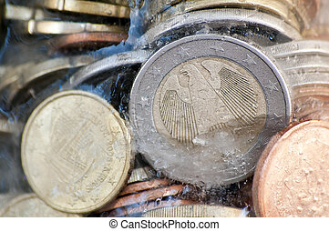 Shiny euro coins frozen in ice with german coin in front -...