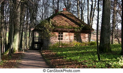 Old house in autumn forest - Log cabin in autumnal city park...