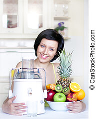 young woman with a juicer in the kitchen