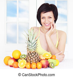 young woman with fruits on light background