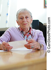 Portrait of a senior woman at home sitting at the table with...