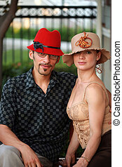 Stylish young couple in beautiful designer hats.