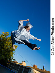 Happy young graduate doing high jump kick, blue sky behind