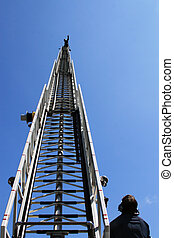 Fire ladder extended high with fireman on top waving hand