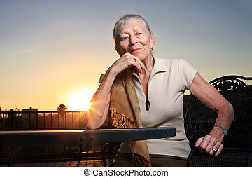 Senior woman sitting at the table outdoors at sunset