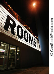 "Shining neon sign ""Rooms"" on a hotel at night."