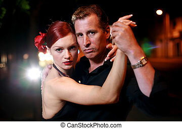Couple dancing on a street at night. Shallow DOF.