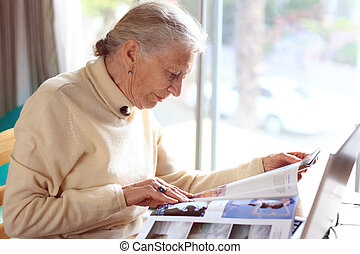 Elderly lady reading magazine. Shallow DOF.