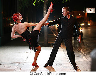 Couple dancing on a street at night.