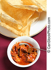 Mango pickle and pappadum vertical - A bowl of spicy green...