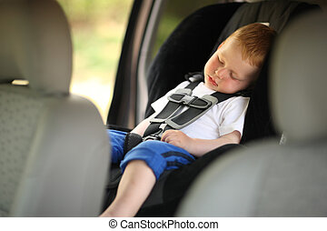 Boy sleeping in child car seat. Shallow DOF.