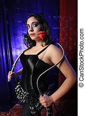 Beautiful girl with whip in hands and red rose in mouth.